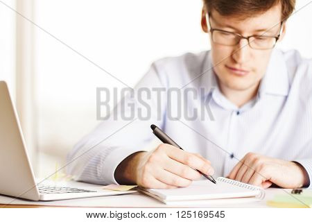 Frontview of focused businessman writing in notepad at desk with laptop