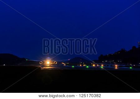 Front view of Passenger Airplane at landing strip in the night