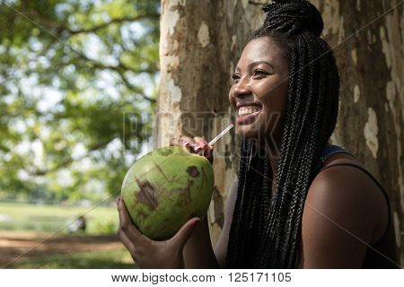 Brazilian woman drinking coconut water in the park