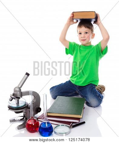 Small boy holds a big book on his head. Isolated on white background
