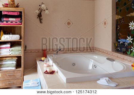Comfortable spa-style slippers beside the jacuzzi bathtub in home bathroom.