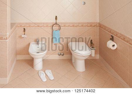 Spa-styled slippers beside the bidet inside home bathroom.