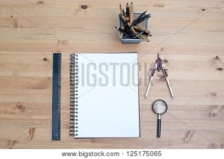 Workplace artist top view. Stationery with a notebook on a wooden table.