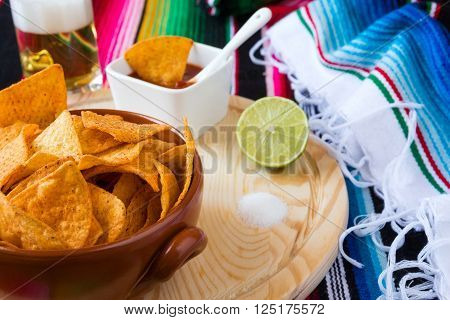 Nachos chips in a bowl over a chopping board with tomato sauce beer lime and salt with poncho background