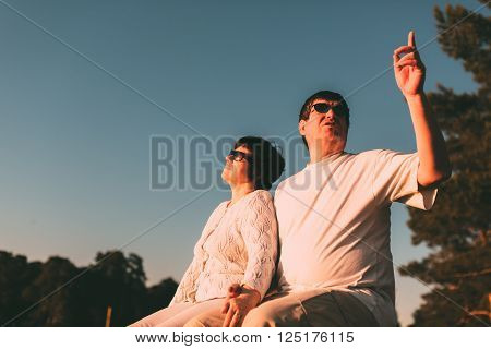 Adult couple sitting on a bench and looking at the sky. Side view photo.