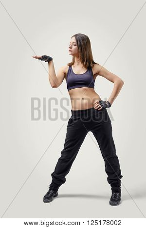 Full body portrait of young girl dancer looking at her raised right hand palm up. Left hand on her hip. Front view.