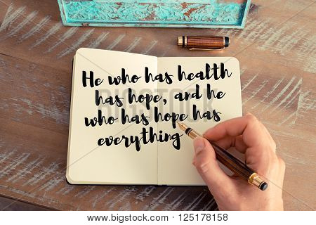 Retro effect and toned image of a woman hand writing on a notebook. Handwritten quote He who has health has hope, and he who has hope has everything as inspirational concept image