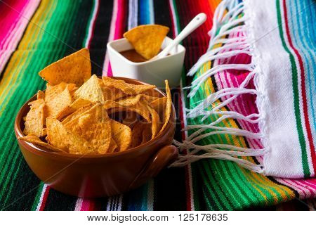 Nachos chips in an earthenware bowl and tomato sauce over a colored poncho