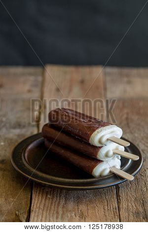 popsicle with grated chocolate on a wooden background