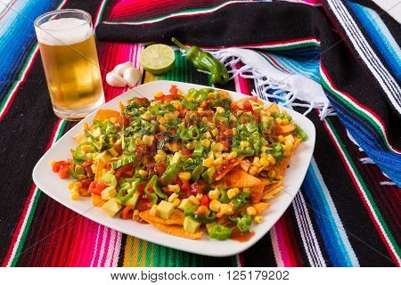 Nachos salad and beer in a square plate over a colored poncho