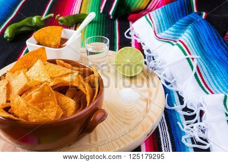 Nachos chips tequila lime and salt over a chopping board with a colored poncho background