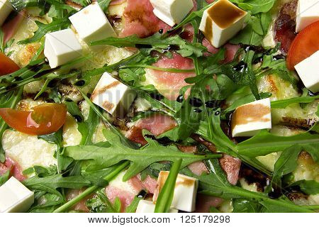 Appetizing pizza with ham, salami, arugula, cherry tomatoes, fetaksa, balsamic closeup