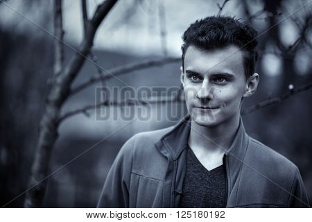 Monochrome toned portrait of a handsome teenage boy outdoor