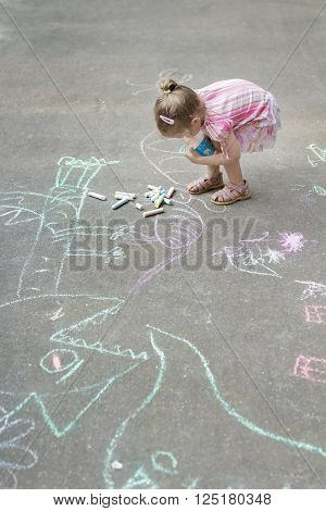 Overhead shot of little Caucasian girl is chalking on hopscotch yard