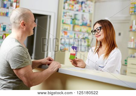Pharmacist Selling Medicine To Customer