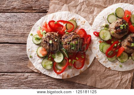 Grilled meat balls with fresh vegetables on a flat bread. Horizontal top view