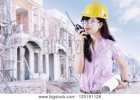 Young female contractor wearing helmet and holding a blueprint at the residential site while talking on the walkie-talkie