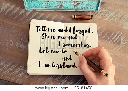 Retro effect and toned image of a woman hand writing on a notebook. Handwritten quote Tell me and I forget. Show me and I remember. Let me do and I understand as inspirational concept image