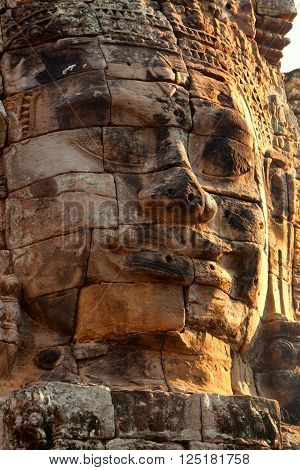 Dramatic view at sunset of one stone carved faces of Bayon Temple in Angkor Thom Angkor district Siem Reap Cambodia