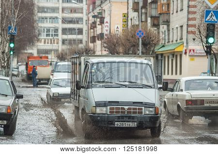 Tyumen, Russia - March 22, 2005: Cars splash through large puddle on flooded street