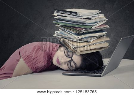 Photo of a stressful young businesswoman sleeping over a laptop with a stack of documents on her head