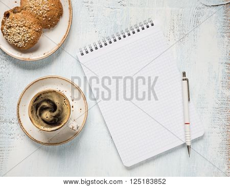 Black coffee with crema in vintage porcelain cup checkered notepad; pencil and oatmeal cookie on a light wooden background top view
