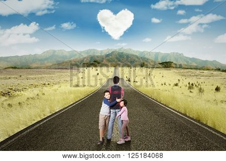Picture of two children hugging their daddy on the road with cloud shaped heart symbol