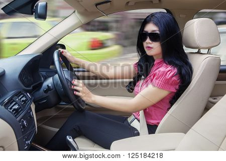 Successful young businesswoman driving a new car while wearing sun glasses