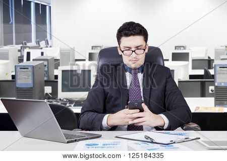 Portrait of Arabian male entrepreneur reading a message on his cellphone while working with a laptop in office room