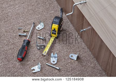 Hand tool, Screwed furniture screw, Screwdriver with screws and metal hinges, tape measure, all for assembling furniture.