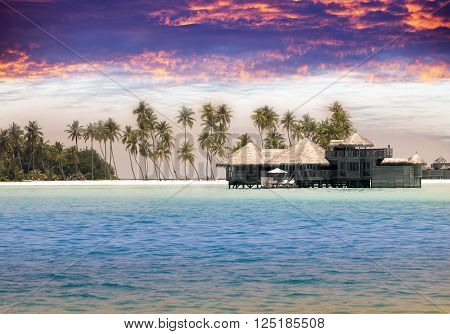 Maldives. houses on piles on water at the time sunset.