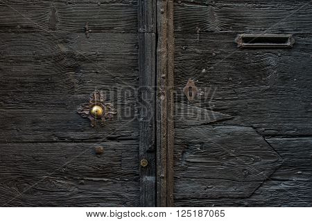 Old medieval  italian wooden door with metal handle and a mail slot