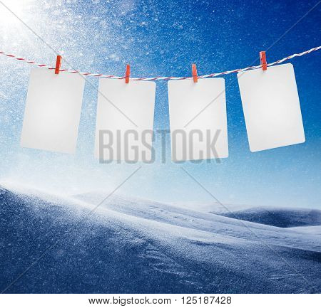 Blank paper or photo frames hanging on the red striped rope. Snowstorm in sunny day on background.