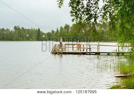 Cloudy summer day on the lake. Wooden boat dock overlooking the water and island. Area for summer camping in the woods. Purhon Campsite, Hamina, Finland, Suomi