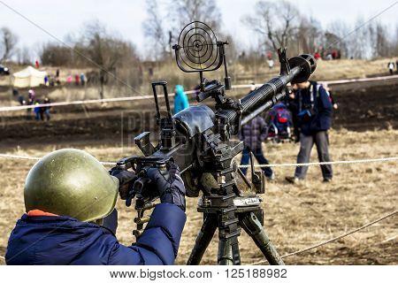 April 03 2016. Saint-Petersburg.Boy in military helmet to aim the gun at the military-Patriotic festival