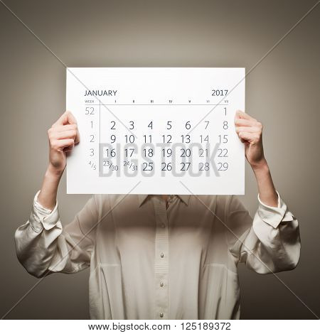 Woman is holding January calendar of the year two thousand seventeen.