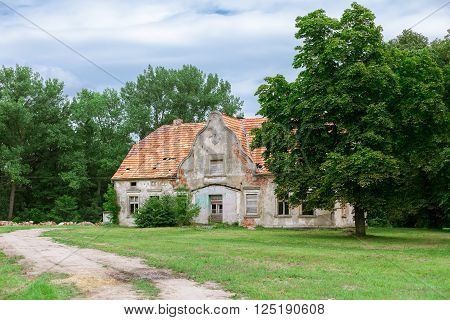 Old abandoned and rundown house between trees