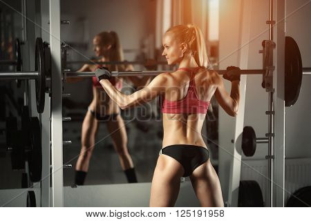 Beautiful fitness sexy woman doing squat workout in gym. Fitness, sport, powerlifting and people concept - sporty woman exercising with barbell in gym