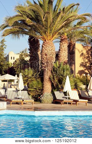 Resort hotel with sun beds palm trees and swimming pool