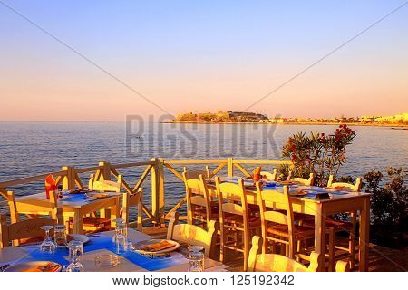 traditional greek outdoor restaurant on terrace with sea view at street village restaurant, Crete, Greece. Sunset light