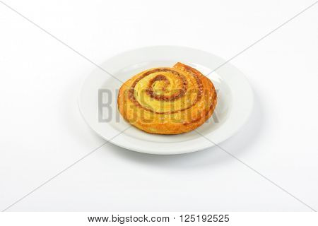 sweet cinnamon roll on white plate