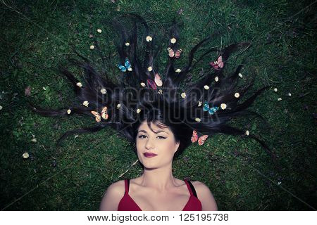 Beautiful woman with long widespread hair lying on a meadow with daisy and fake colorful butterflies in the hair