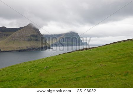 Typical landscape on the Faroe Islands with green grass and rocks close to Vidareidi