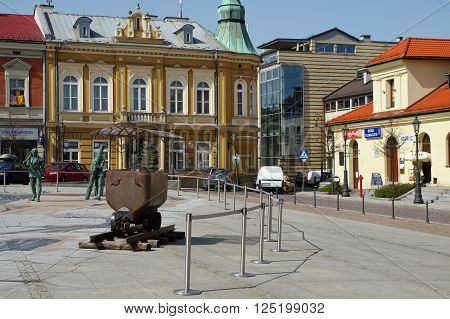 Wieliczka, Poland - April 04, 2016: Upper Square. The historic trolley to transport salt in a salt mine and sculptures of ancient miners salt. In the background are the town houses.