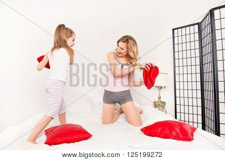 Happy Mother And Daughter Having Fun And Fighting With Pillows