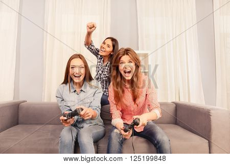 Three Happy Attractive Girls Sitting On Sofa And Playing Video Games