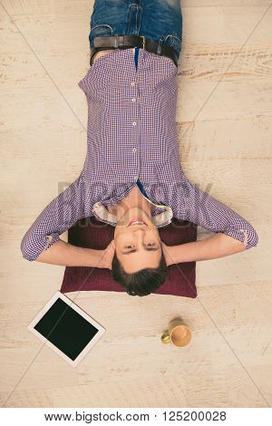 Top View Photo Of Smiling Man Lying On The Floor With Cup And Tablet