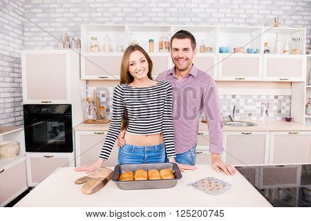 Smilling Young Couple In Love In The Kitchen With Baked Cakes