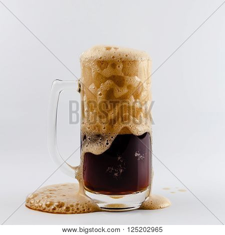 Pouring process of dark stout beer into a beer glass mug splashes drops and froth around glass mug against white background