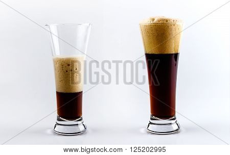 Set of two beer glasses. Pouring process of dark stout beer into a beer glass splashes drops and froth around glass against white background